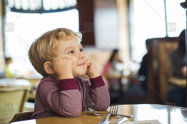 Little blond boy sitting at table in wonderment