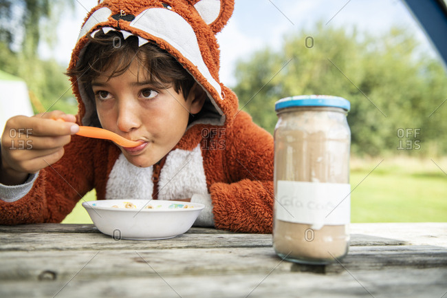 Boy having breakfast on a campsite excursion