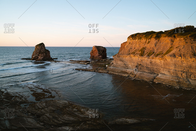 Two big rock formations on the coast of France during golden hour
