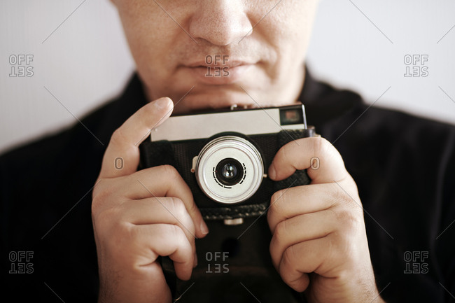 Close up of a man holding a vintage film camera