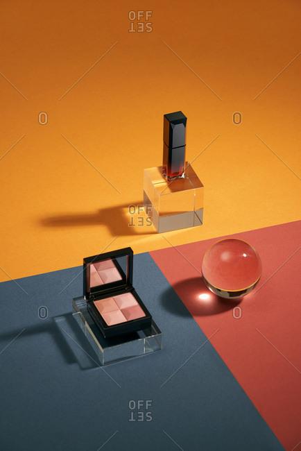 Set of eyeshadows, lipstick. Fashion woman still life. On color background