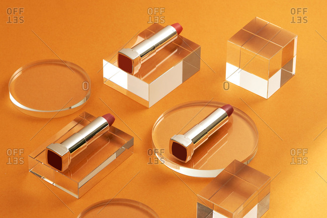 Flat lay fashion with lipsticks, Essential beauty item on color orange background