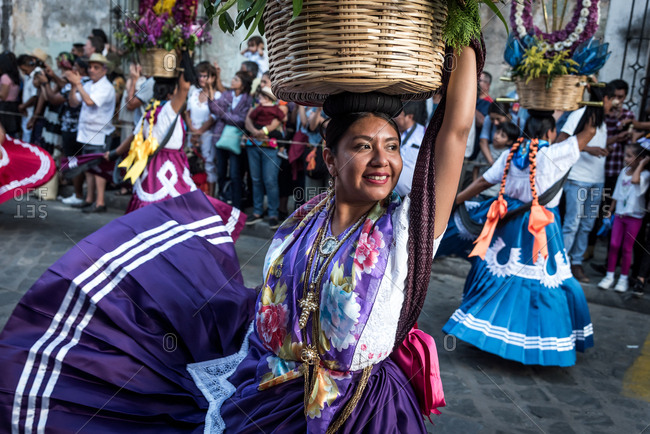 July 28, 2019: A china oaxaquena dances balancing a basket with flowers on her head during the Guelaguetza parade in Oaxaca, Mexico