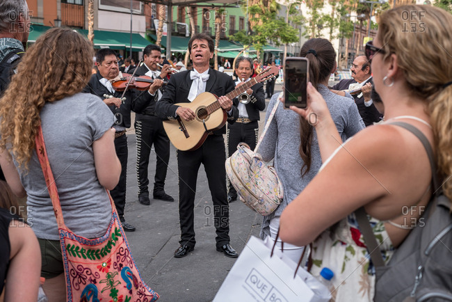 July, 23, 2019: A mariachi band plays in front of some tourists in Garibaldi Square, Ciudad de Mexico, Mexico