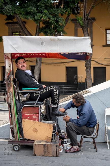 July, 23, 2019: A shoe polisher cleaning a Mariachi's shoe in Garibaldi Square, Ciudad de Mexico, Mexico