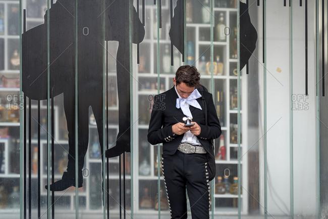July, 23, 2019: A Mariachi texting with his smartphone in Garibaldi Square, Ciudad de Mexico, Mexico