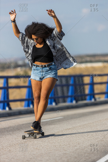 Young and afro woman skating on a long board by an empty bridge at sunset, front view
