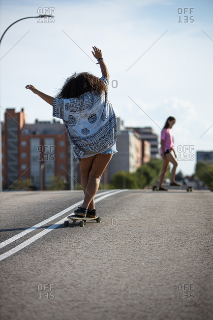 Young and afro woman skating on a long board by an empty bridge at sunset, back view