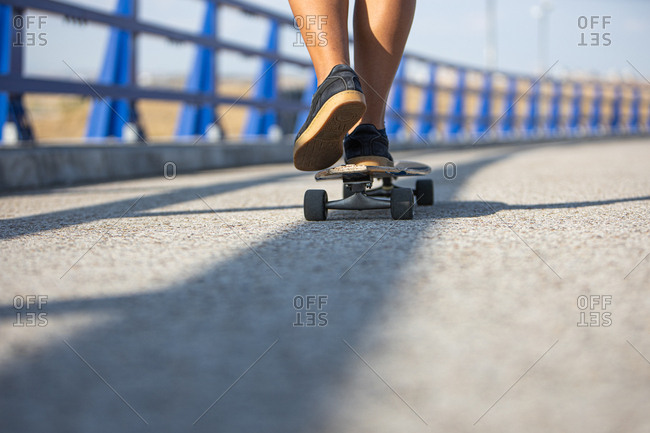 Women feet skating on a long board by an empty bridge at sunset, back view