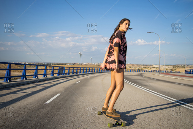 Beautiful young woman skating on a long board by an empty bridge at sunset