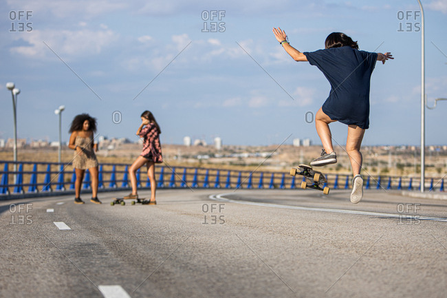 Unrecognizable young woman doing a trick with her long board by a bridge with her companions in the background