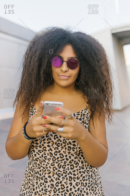 Young and afro woman with sunglasses chatting with her smart phone