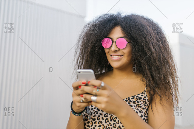 Young and afro woman with sunglasses chatting with her smart phone and smile