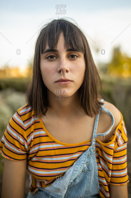 Caucasian young woman with nose piercing looking serious at camera