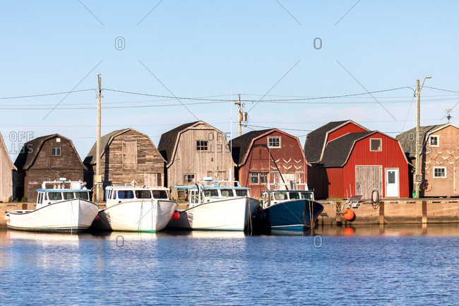 A line of oyster barns and fishing boats at Malpeque Harbor on the north shore of Prince Edward Island (PEI) , Canada
