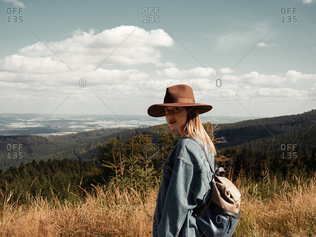 Woman in hat looking on nature, forest and clouds