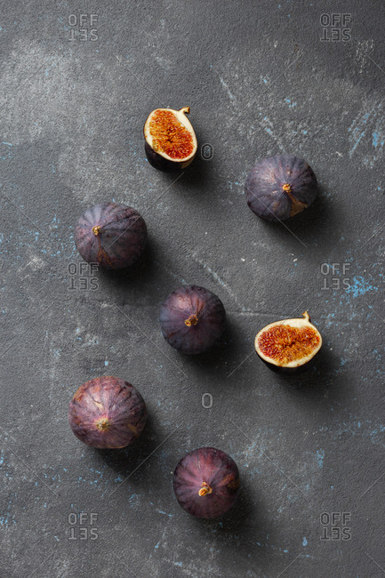 Organic sliced and whole fresh figs on dark background