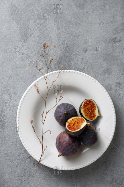 Sliced and whole fresh figs in bowl on light background top view