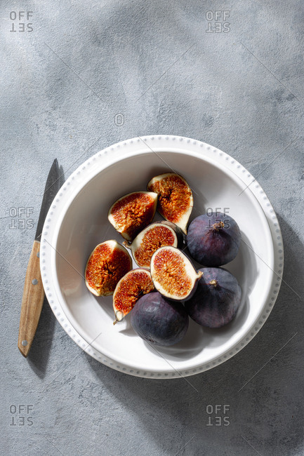 Overhead view sliced and whole fresh figs in bowl on light background