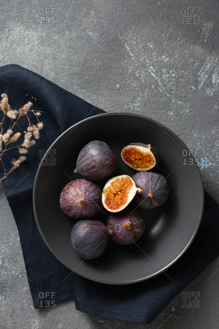 Overhead view organic sliced and whole fresh figs in bowl on dark background