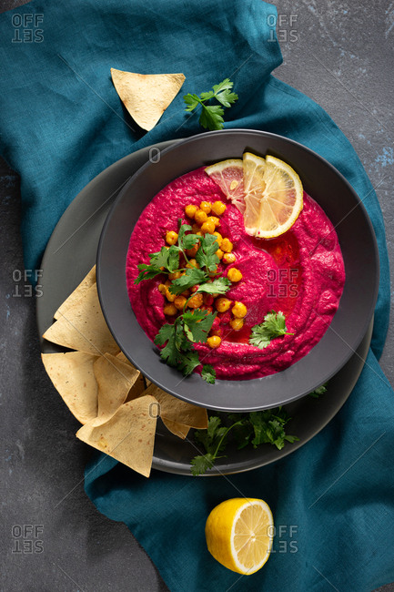 Beetroot hummus in plate with pita bread on dark background