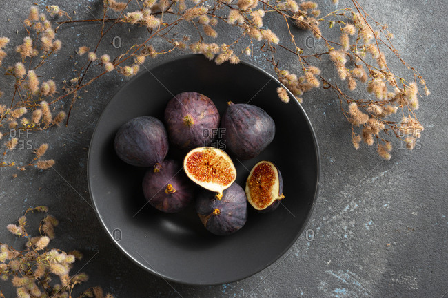 Organic sliced and whole fresh figs in bowl on dark background