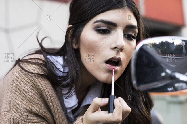 Portrait of young woman applying lipstick outdoors