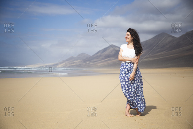 Happy woman standing on the beach looking at distance- Fuerteventura- Spain