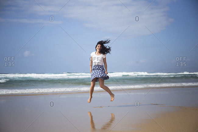 Laughing woman jumping in the air on the beach- Fuerteventura- Spain