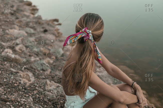 Rear view of young blond woman sitting at a lakeside- hair with cloth