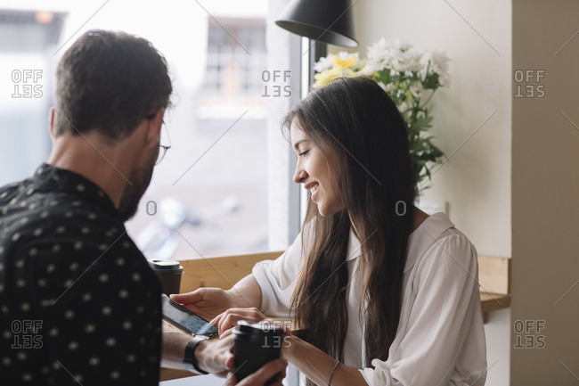 Young couple with disposable cup and smartphone in a cafe