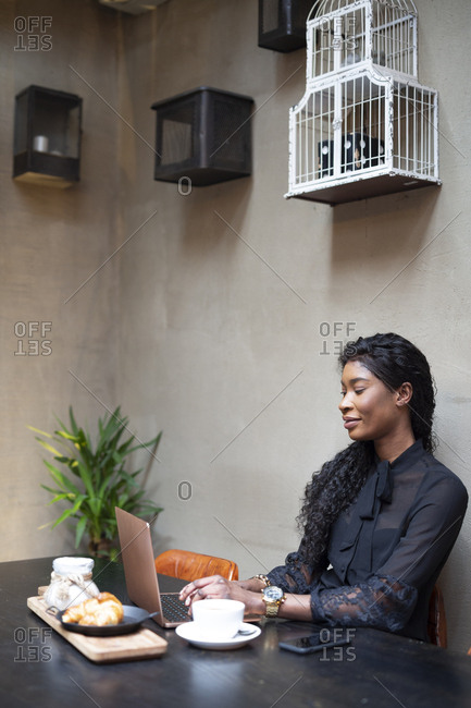 Chic businesswoman using laptop at table in a cafe