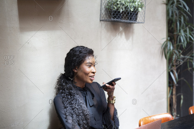 Smiling chic businesswoman using smartphone in a cafe