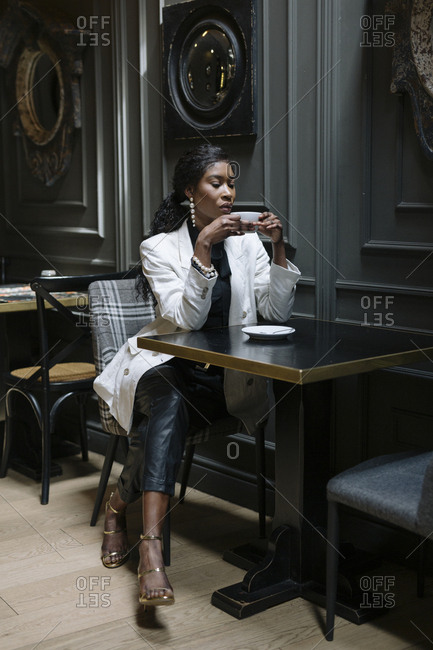 Chic woman drinking coffee at table in a cafe