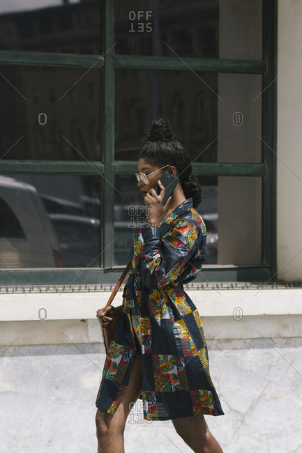 Portrait of chic woman wearing patterned dress talking on cell phone