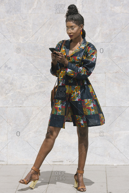 Portrait of chic woman wearing patterned dress using cell phone