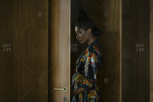 Portrait of chic woman wearing patterned dress at a wooden door