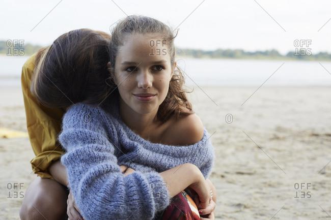 Teenage girls embracing on beach