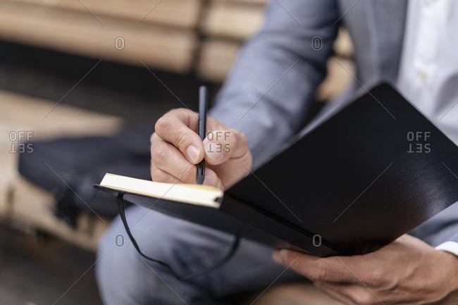 Close-up of businessman writing into notebook
