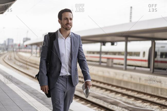 Businessman walking on station platform