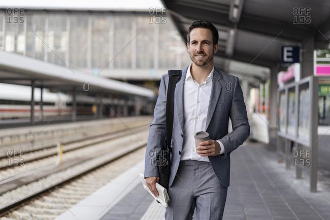 Businessman with takeaway coffee walking on station platform