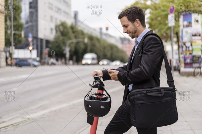 Businessman with e-scooter using cell phone in the city