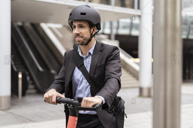 Portrait of businessman with e-scooter in the city