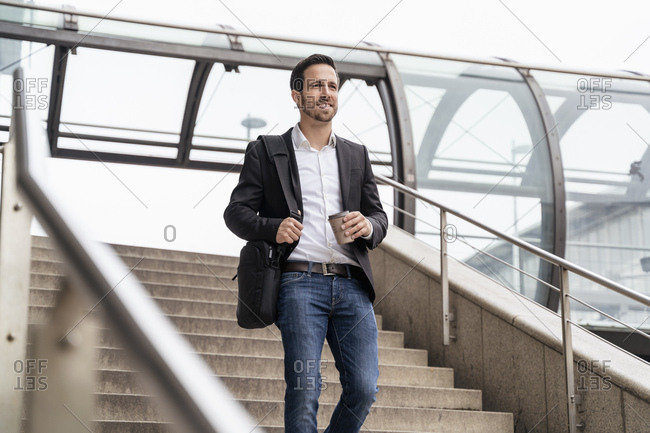 Businessman with takeaway coffee walking on stairs in the city