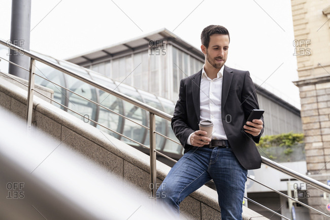 Businessman with takeaway coffee using cell phone in the city