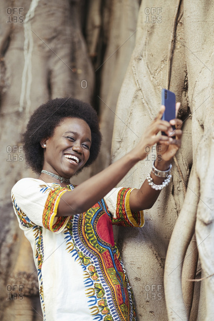 Laughing young woman taking a selfie with a smartphone
