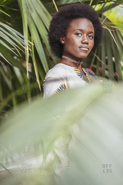 Young woman standing among tropical plants