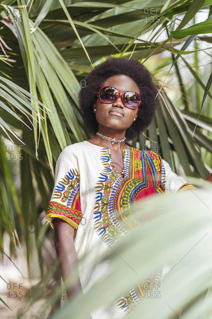 Cool young woman wearing sunglasses posing among tropical plants