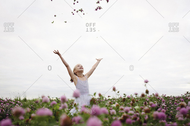 Girl standing in clover field- throwing flowers