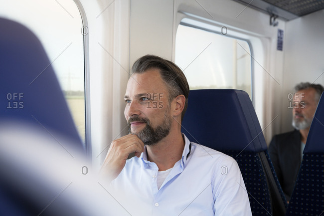 Mature man sitting in a train- looking out of window